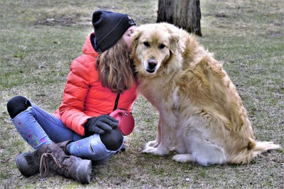 girl cuddling golden retriever dog